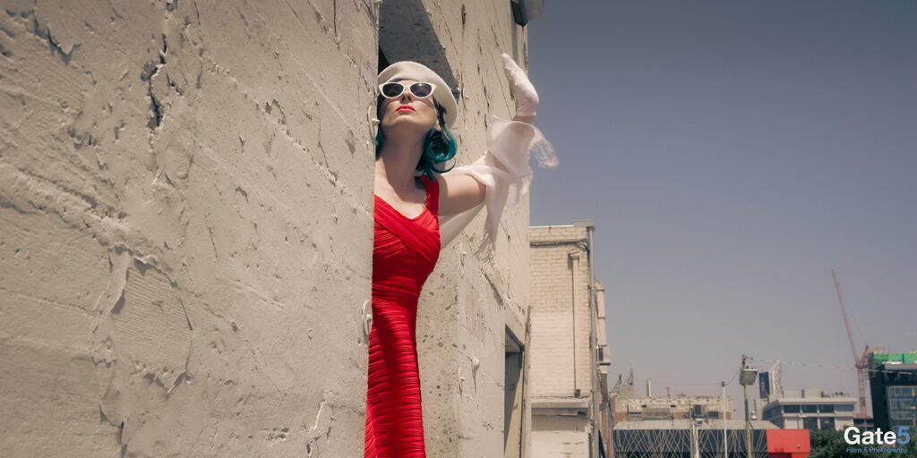 a french woman waves in a red dress from a door in a building